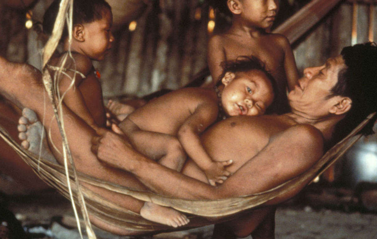 Yanomami family gathered around a hammock made from banana tree fibers.