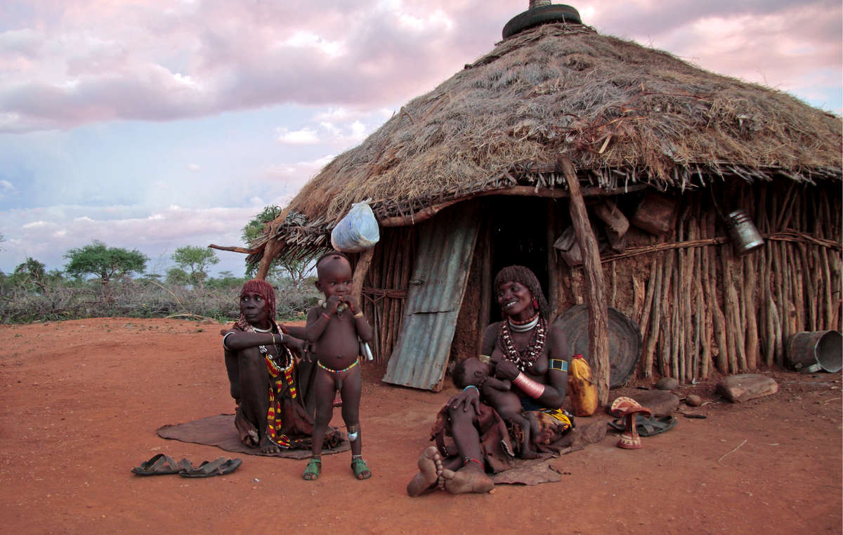 A Hamar family sit outside their home, Omo Valley, Ethiopia. The Gibe III dam that is being constructed will destroy their people's livelihood.