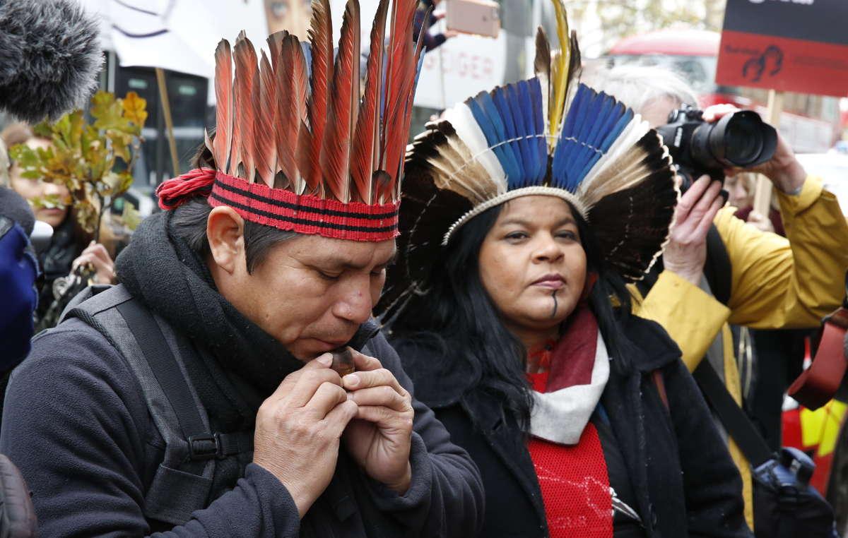Elizeu Guarani Kaiowá toca un silbato indígena ante la embajada de Brasil en Londres.