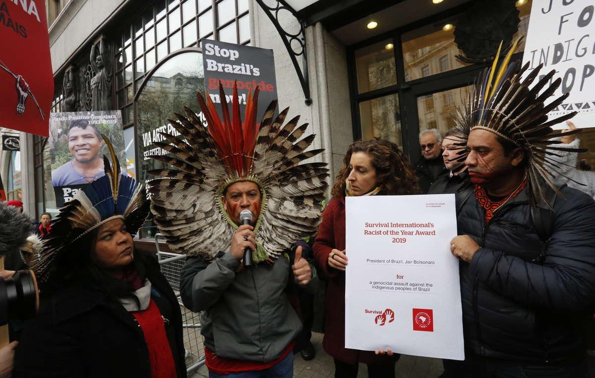 La delegación de APIB y Survival entregan el premio Racista del Año para el presidente Bolsonaro en la embajada brasileña en Londres.