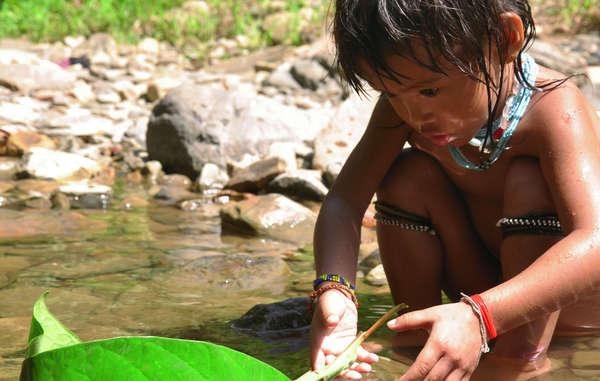 Ein Penan-Kind spielt an einem Fluss mit einem selbstgebauten Boot. Staudämme in der Region bedrohen das Überleben der Penan.