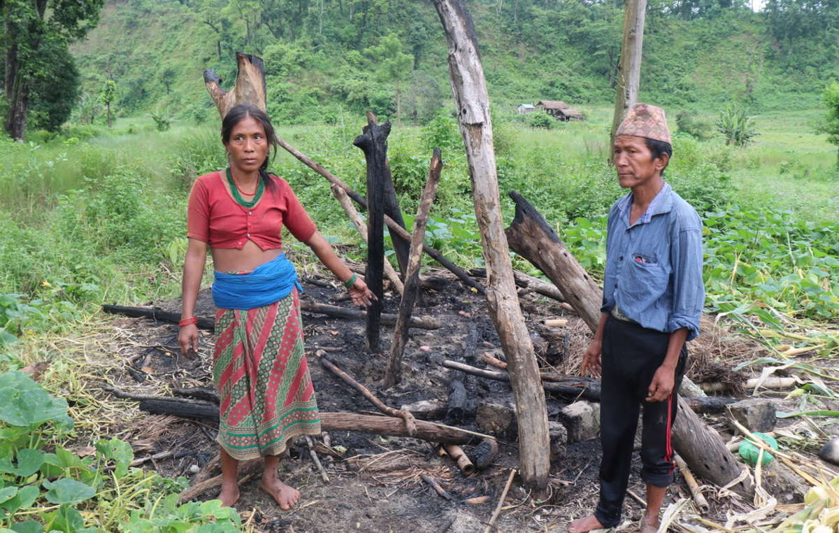 A Chepang family stand in the remains of their house after it was burnt down by officials of Chitwan National Park, Nepal, during the monsoon.