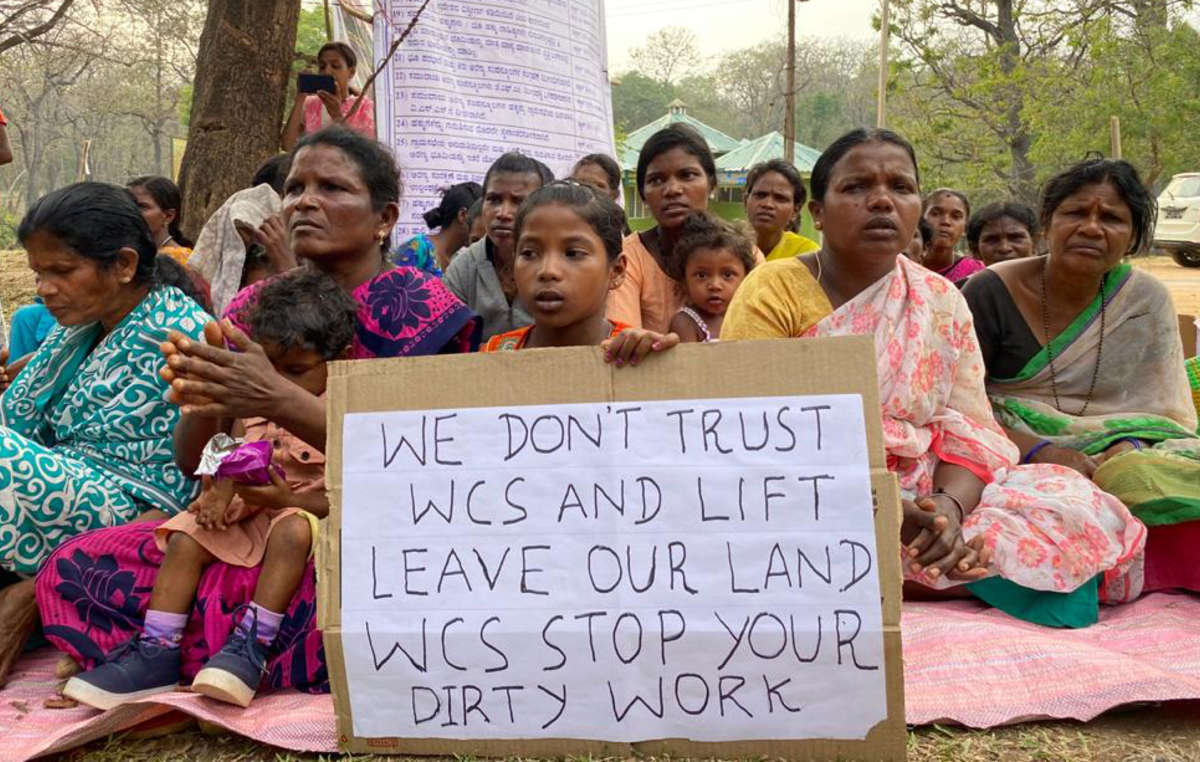 """Indígena Jenu Kuruba segura cartaz que diz: """"WCS, pare com o trabalho sujo"""""""