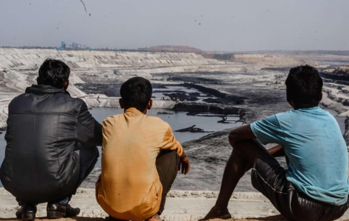 Hombres adivasis miran hacia la inmensa mina de carbón de PEKB que ha destruido gran parte de su tierra ancestral (bosque de Hasdeo, Chhattisgarh).