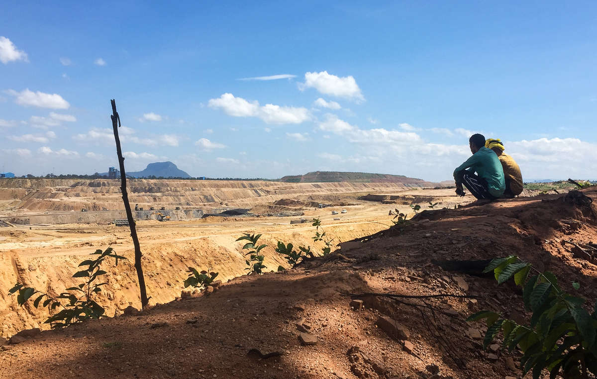 Two Adivasi men look out over an apocalyptic landscape – the vast coal mine that has replaced their ancestral forest. PEKB Mine, Hasdeo Forest, Chhattisgarh.