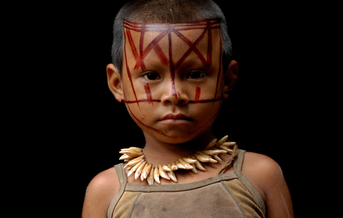 A Nukak child wearing a necklace made from monkey teeth.