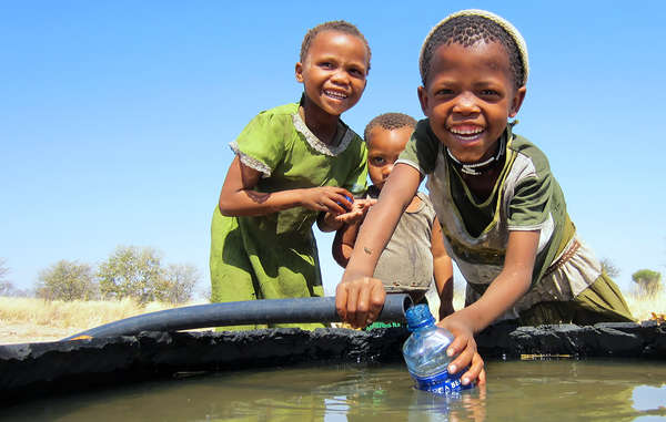 Bushmen girls playing with water from the Mothomelo borehole on the Central Kalahari Game Reserve, Botswana.