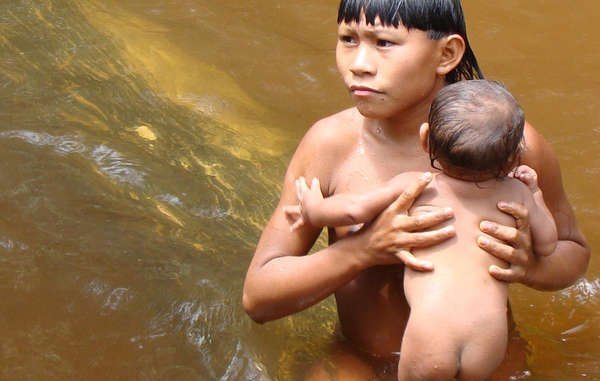 A Suruwaha boy bathes a young baby in a stream.