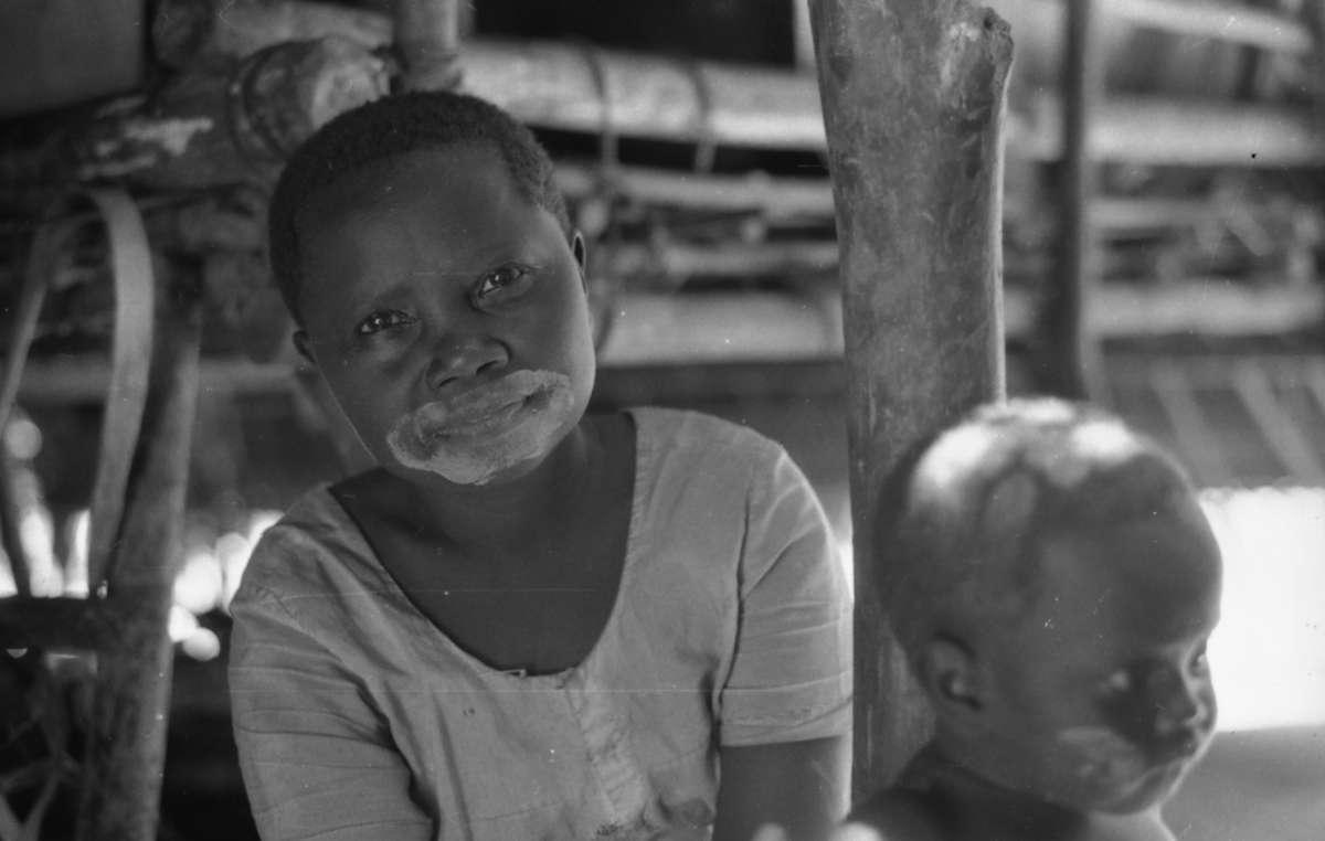 Frau der Onge mit Kind. Die Onge malen ihre Körper, einschließlich ihrer Gesichter, mit weißer Kreide an.