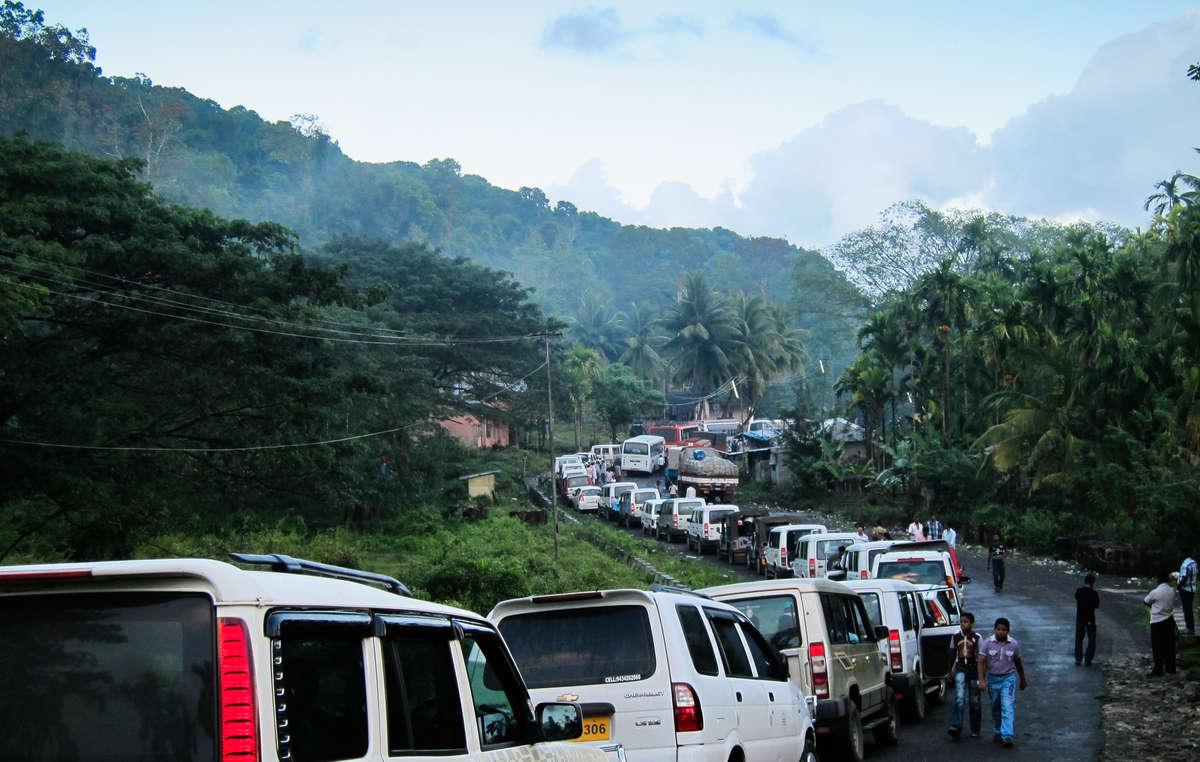 Autos stehen Schlange, um entlang einer illegalen Straße in das Jarawa-Reservat zu fahren.