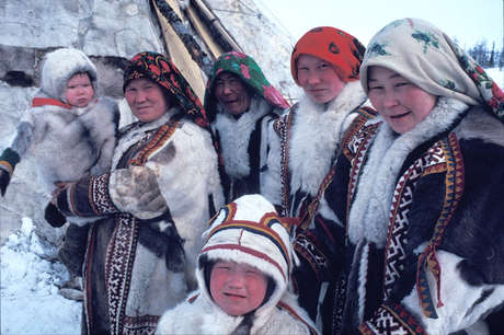 Khanty women and children outsider their Chum – a house made from reindeer skin which is packed up and taken with them when they follow the reindeer's migration.