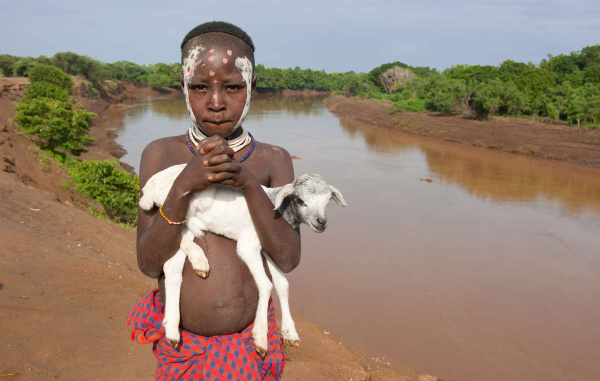 A boy from the Lower Omo stands on the riverbank.