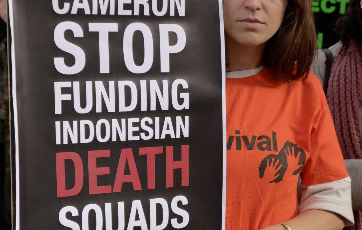 Protester holding banner reading 'Cameron stop funding Indonesian death squads' to mark the visit of Indonesia's President to the UK.