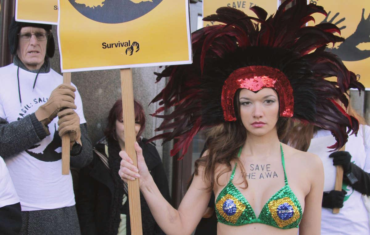 Mulher vestindo trajes carnavalescos em Londres, carregando uma mensagem ao Brasil: Salve os Awá