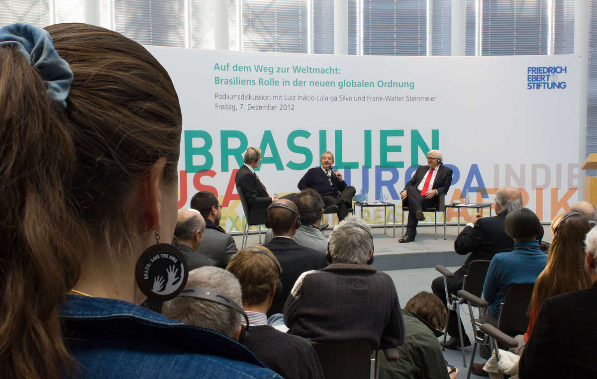 Mulher com brincos Brasil: Salve os Awá assistindo uma palestra do ex-Presidente Lula