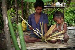 Batak-Mutter und Kind teilen Bambus, Palawan, Philippinen