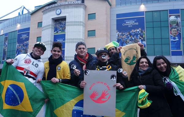 Brasilianische Fussballfans halten das Awá-Symbol 'Brazil: Save the Awá' hoch.