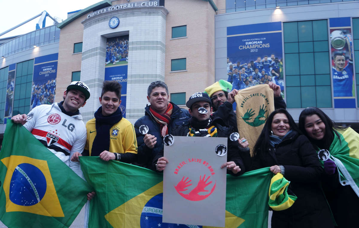 Fãs brasileiros de futebol brandindo o iconeAwá, onde se lê Brasil: Salve os Awá.