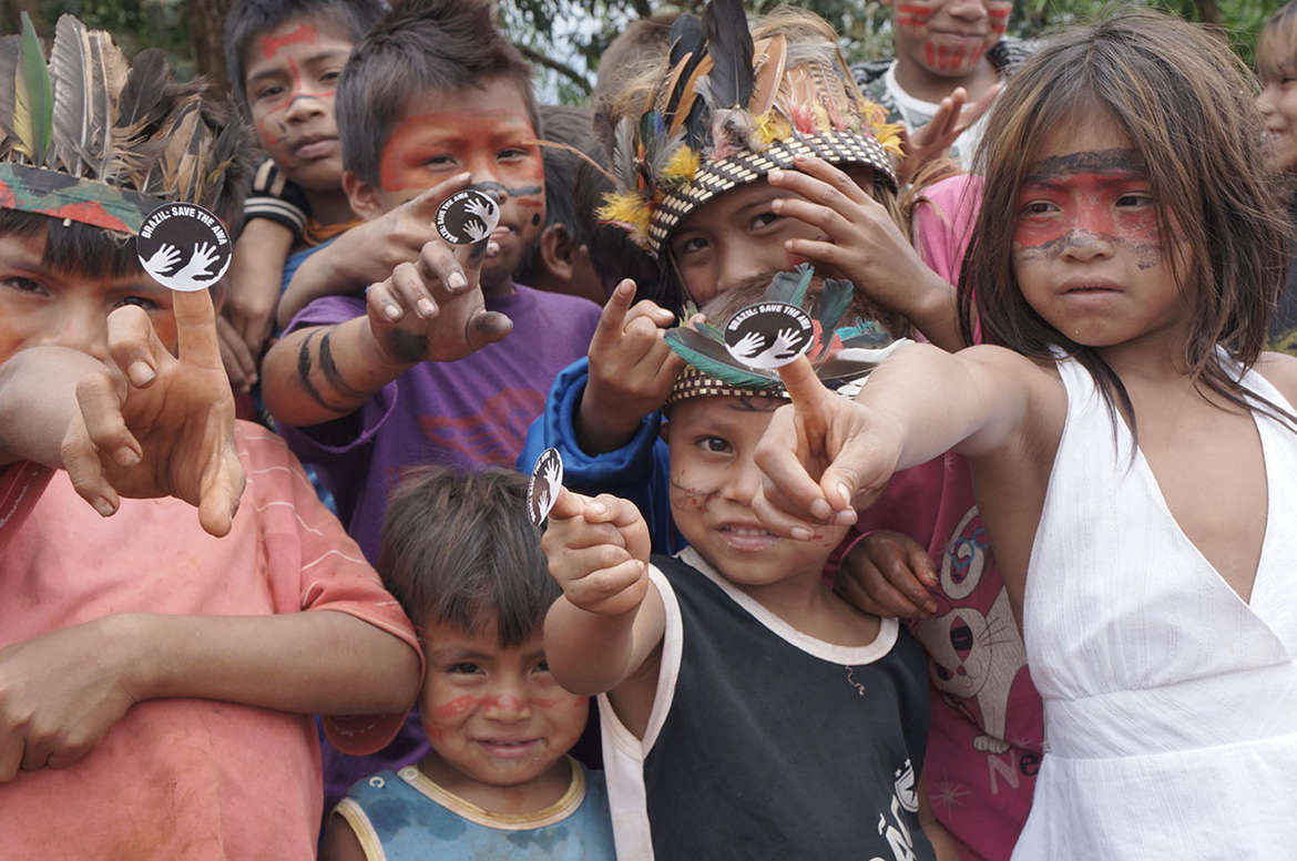 Guarani children with the Awáicon sticker. The Awáicon is used all over the world to show support for the Awá.