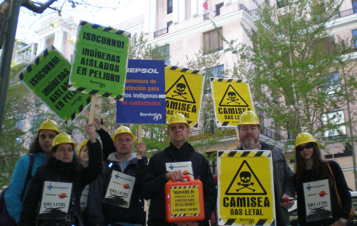 Protesters in Madrid wearing helmets and carrying placards to symbolize the lethal effects of the Camisea project on Peru's uncontacted tribes.