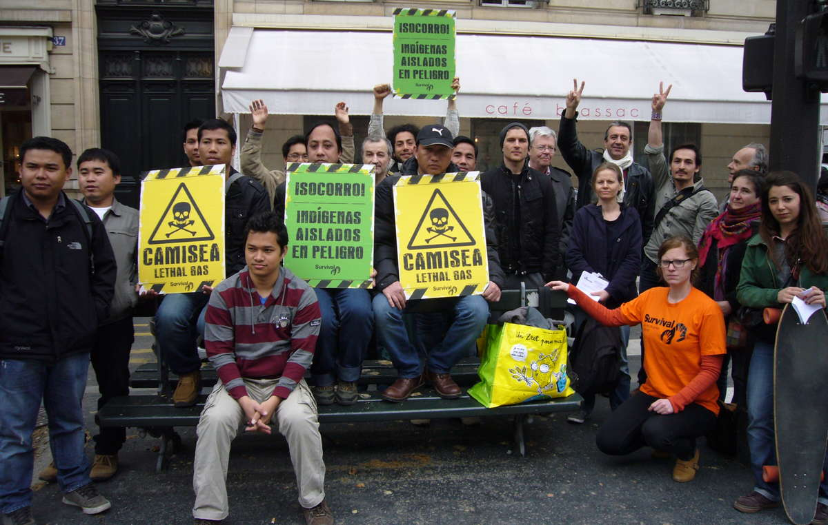 Protesters in Paris were carrying placards to symbolize the lethal effects of the Camisea project on Perus uncontacted tribes.