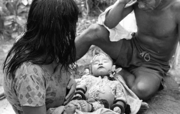 A Karajá couple with their baby, who has died of flu, Brazil.
