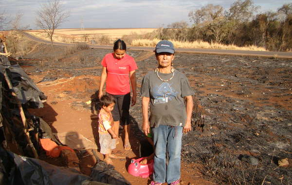 Damiana, leader of Apy Ka'y community, stands by the remains of their camp after it was destroyed by fire.