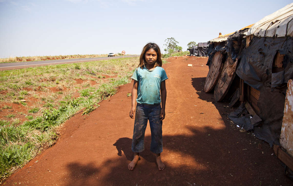A Guarani girl stands by her road-side shack – endless fields have replaced her tribes rich forests. Children as young as nine have been committing suicide.