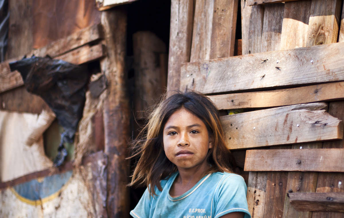 A nine-year-old girl stands alongside her makeshift home in the Guarani roadside camp of Apy Ka'y, located in the Brazilian state of Mato Grosso do Sul. The Guarani are frustrated with the Brazilian government's delay in returning their ancestral lands to them.