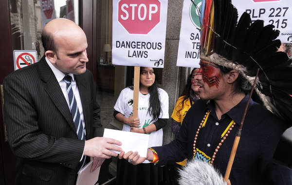 Nixiwaka Yawanawá from Brazil's Amazon hands a protest letter to an embassy official.