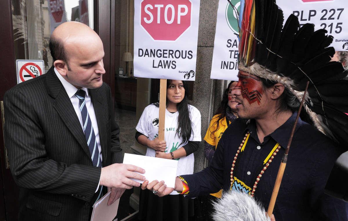 Nixiwaka Yawanawá, dAmazonie brésilienne, remet une lettre de protestation à un employé de lAmbassade.