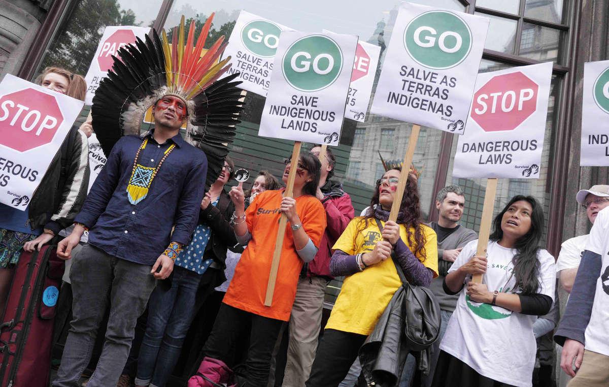 Les manifestants ont brandi des pancartes demandant au Brésil de renoncer aux lois qui menacent les territoires indigènes.