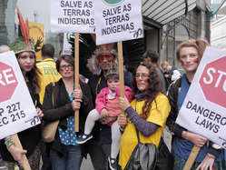 """""""Protestors held placards telling Brazil to stop dangerous laws and save indigenous lands."""""""
