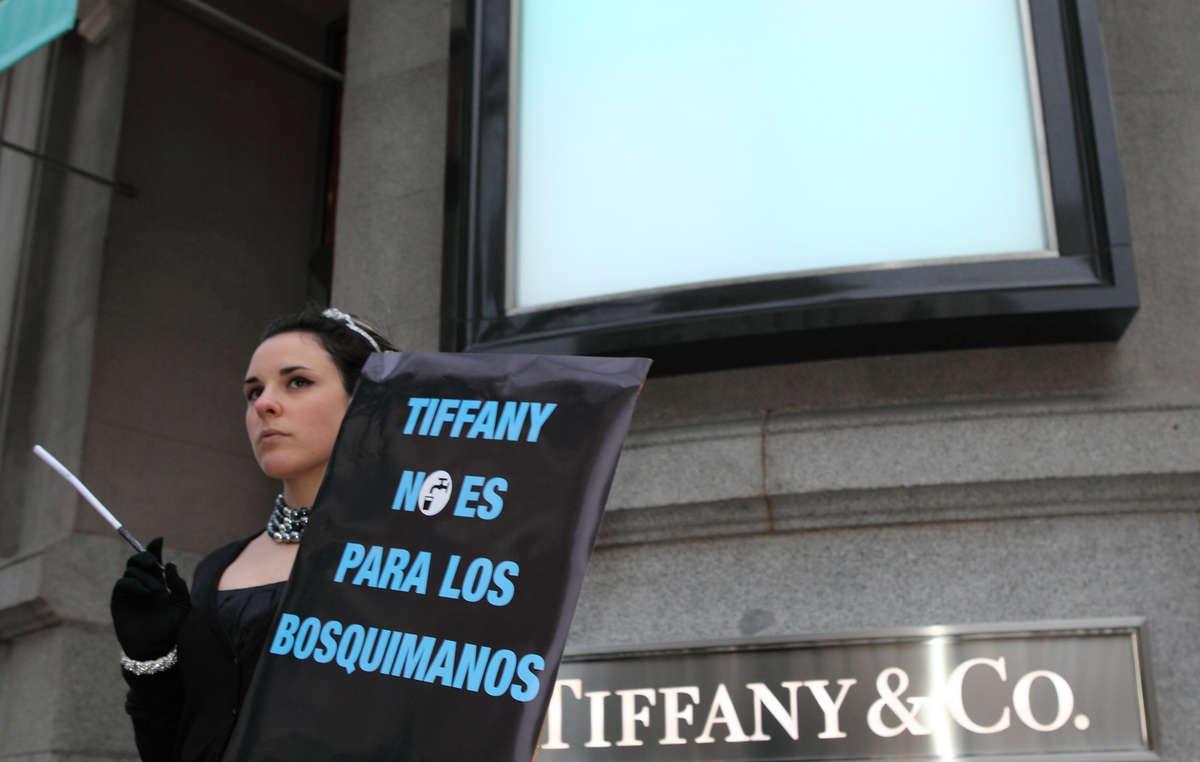 Manifestante disfrazada de Audrey Hepburn con pancarta de protesta ante la tienda de Tiffany en Madrid