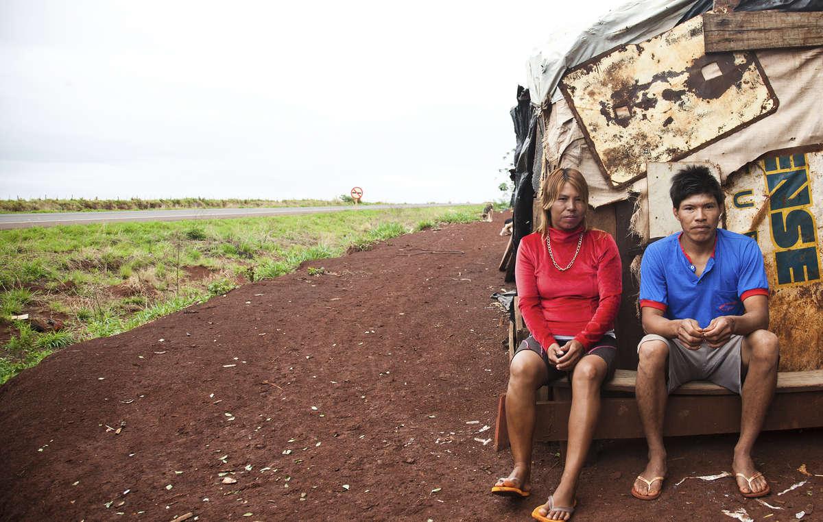 Um casal Guarani-Kaiowa senta-se fora de seu assentamento improvisado à beira de uma rodovia na comunidade Apy Ka'y, próximo de Dourados, Mato Grosso do Sul.