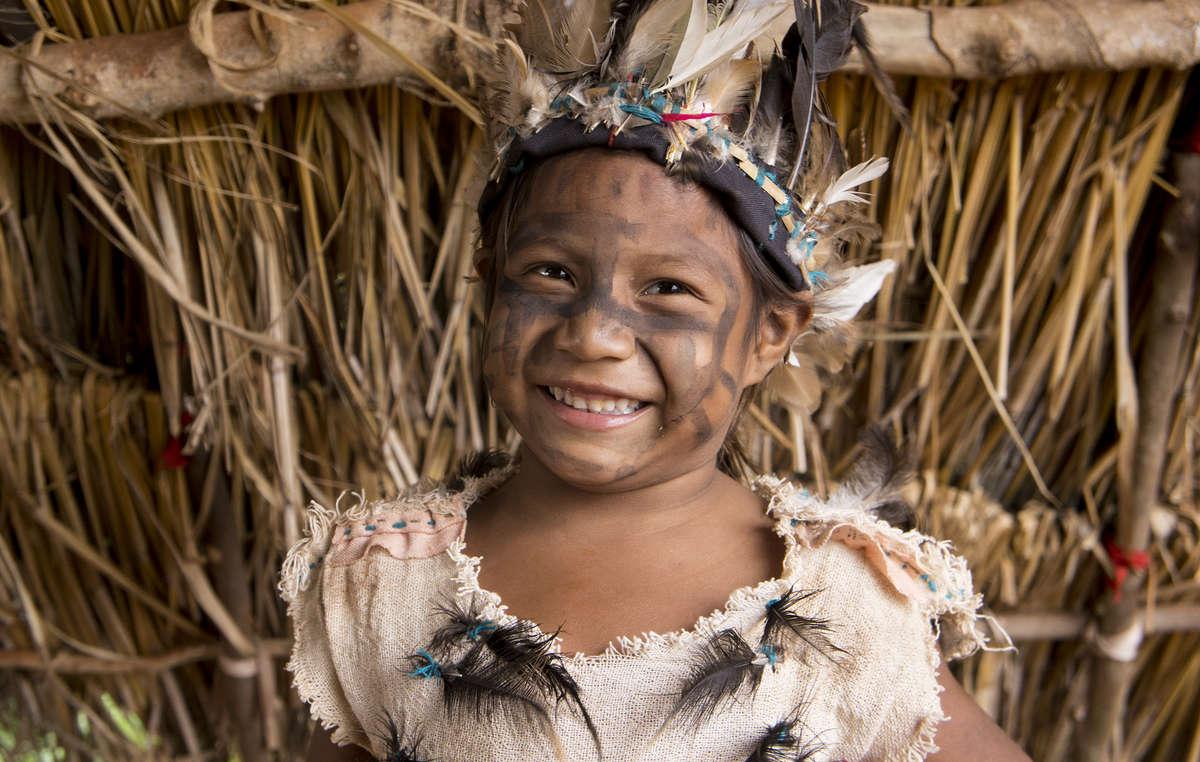 Un enfant guarani de la communauté Guaviry portant des plumes décoratives et de la peinture, Mato Grosso du Sud, Brésil.