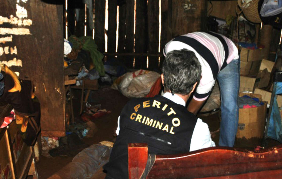 Police officials examine Ambrósios body inside his hut.