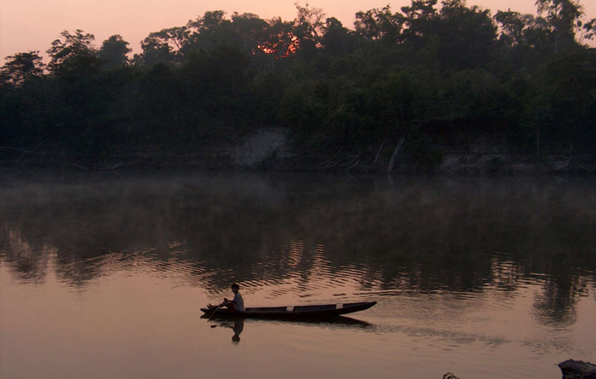 Pirahã man in a canoe at sunset on the Maici river, Brazil. The small Pirahã tribe will be affected by the Madeira river dams in the Western Amazon. These mega-dam projects threaten to devastate the rainforest and the river's ecosystem, as well as destroy the lives, homes and livelihoods of thousands of people who depend upon the river and forest for their survival.