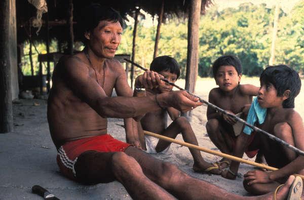 Un hombre waimiri-atroari enseña a los niños cómo hacer una flecha.