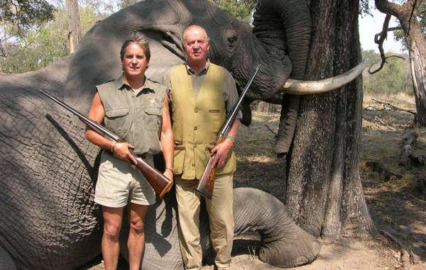 El Rey Juan Carlos I de España posa con el propietario de Rann Safaris frente a un elefante abatido durante una cacería.