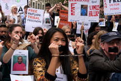 """Protestors outside the Indonesian embassy were handcuffed and had their mouths taped shut."""
