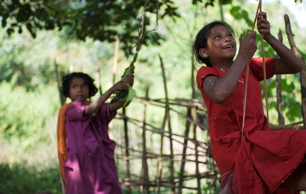 Dongria Kondh children swing from a tree in Niyamgiri, Orissa