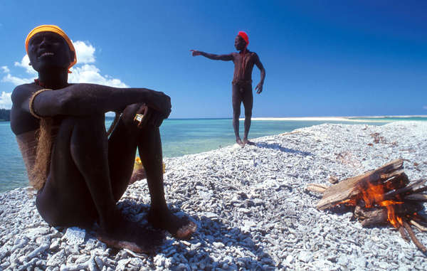 Two Jarawa relax by the coast of the Andaman Islands.
