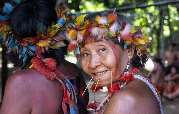 A Yanomami woman wearing brightly coloured macaw feathers at the Seventh Assembly of the Hutakara Yanomami Association, Watoriki.