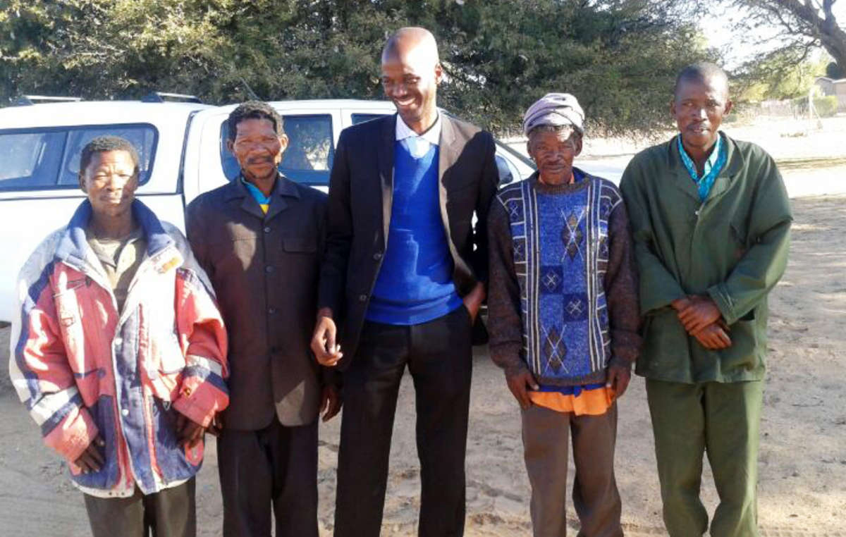 Four Bushmen stand outside court after being cleared from poaching charges, Botswana, 2014. Despite Botswana's High Court recognising the Bushmen's right to live and hunt on their ancestral land, the government has not allowed hunting licenses and continues to persecute those making attempts to feed their families by accusing them of 'poaching'.