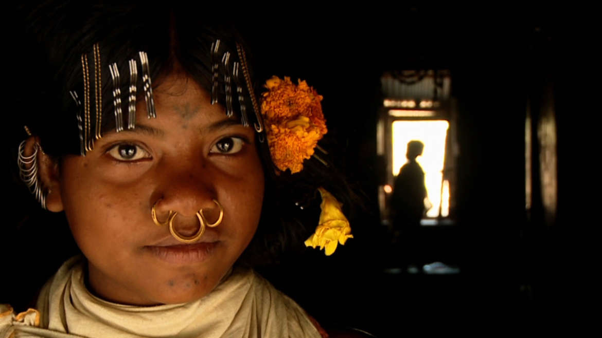 Mitu, a Dongria Kondh girl, outside her house in Orissa, India.