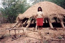 Uma mulher Ayoreo visitando uma casa Ayoreo abandonada por causa do desmatamento, Paraguai.