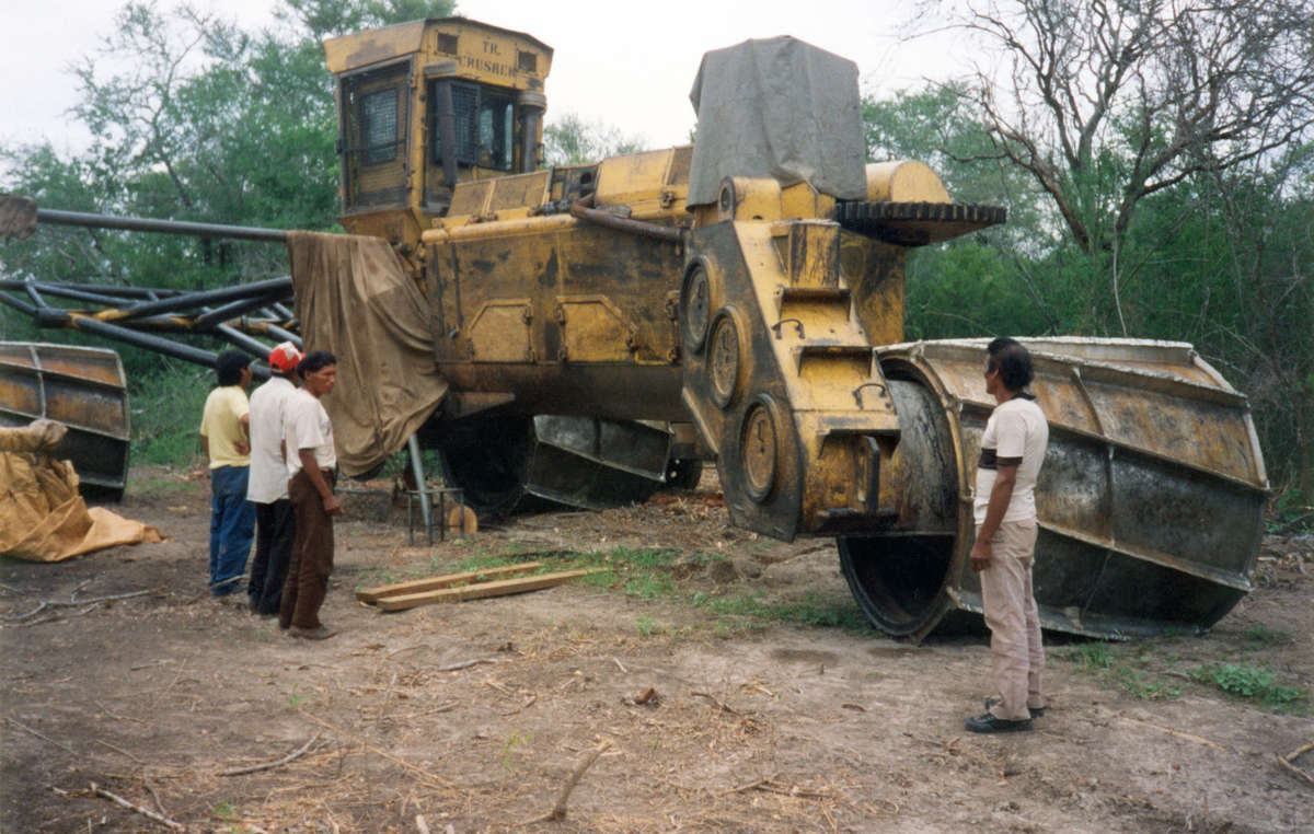 A group of Totobiegosode leaders gaze at one of the enormous bulldozers now destroying much of their hunting territory, Paraguay.